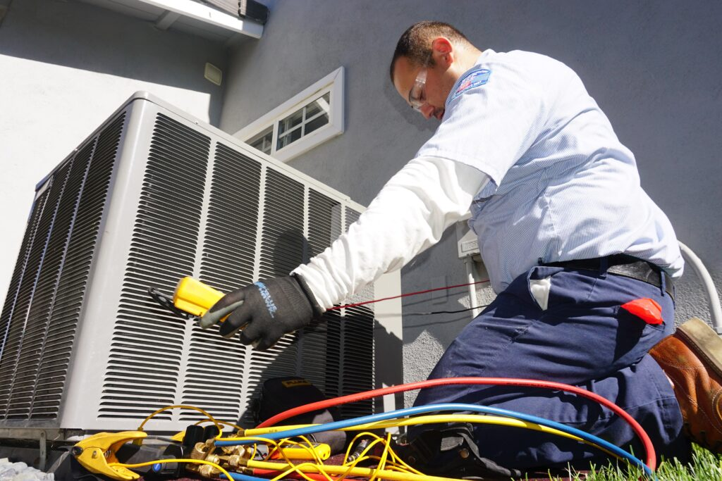 An HVAC technician inspecting an outdoor A/C unit
