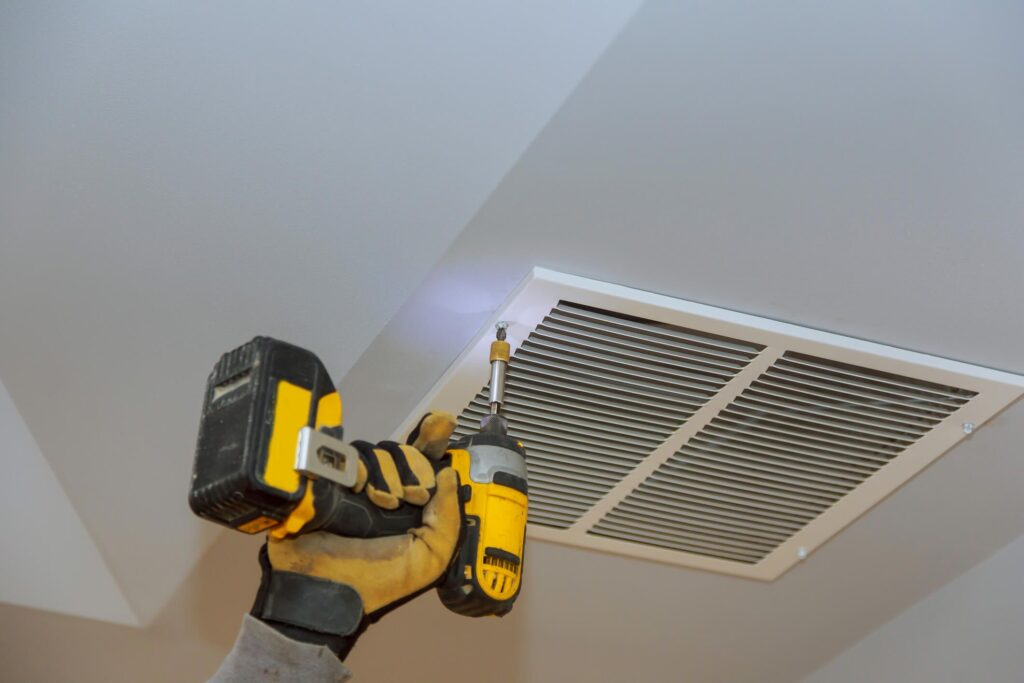 A hand holding a drill that is unscrewing an air vent cover