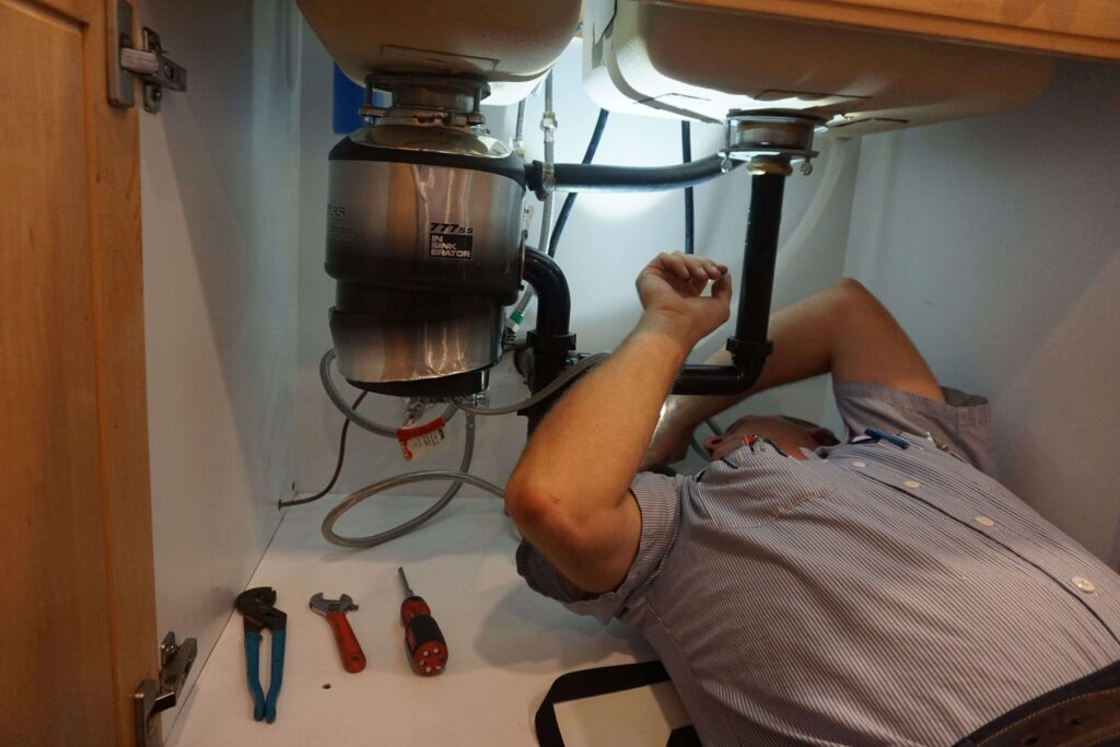 A plumber working under sink