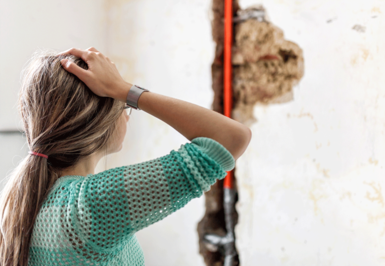 Woman viewing pipe leak damage